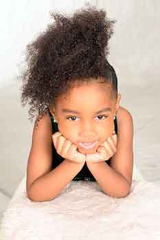 Model With Face in Hands Wearing Afro Curl Ponytail