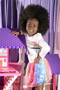 Model Standing By Playhouse: Classic Afro With a Braid in Front Black Hairstyles for Little Girls