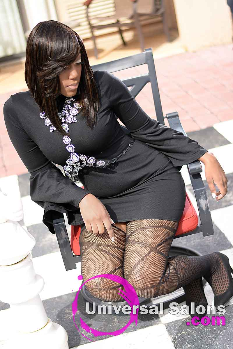 Model Sitting in Chair With Long Diagonal Forward Quick Weave Bob